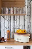 Bread box, vegetables and glasses on shelf against tree-patterned wallpaper