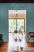 Blick von Wohnzimmer mit blau-grauer Wand in das Esszimmer mit Tisch und Stühlen