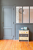 Chest of drawers in front of grey-painted partition wall