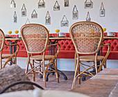Speisesaal mit roter Sitzbank und Vintage Geflechtstühlen