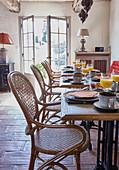 Speisesaal mit gedeckten Frühstückstischen und Vintage Geflechtstühlen