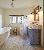 Washstand with countertop sink and free-standing bathtub in rustic bathroom