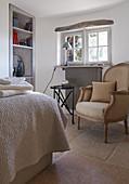 Antiker Sessel mit Kissen, Beistelltisch und Einbauregal in ländlichem Schlafzimmer