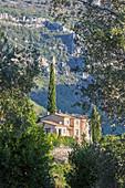 Blick auf Natursteinhaus, umgeben von Berglandschaft