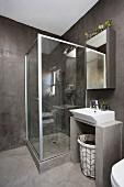 Glass shower cabinet and dark grey walls in bathroom