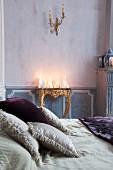 weiße Kerzendekoration mit verschiedenen Motiven auf antikem, vergoldetem Konsolentisch, davor Dekokissen auf Doppelbett