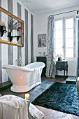 White, free-standing bathtub, grey-striped walls and lattice French windows in cosy bathroom