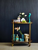 Cocktails, flowers and wine cooler on gilt serving trolley against black-clad wall