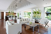 White designer furniture and opulent flower arrangements in open-plan living area of beach house