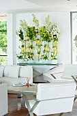 White, leather designer furniture and opulent flower arrangements in lounge area
