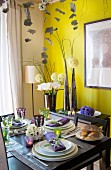 Festively set dining table in front of flower arrangement and yellow wall
