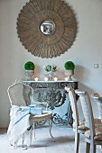 Artistic mirror on wall above festive arrangement on antique console table