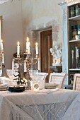 Candles on festively set dining table in historical interior