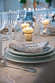 Festive place setting with gold-edged plates, ornate linen napkin and shiny glass pebble