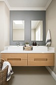 Twin countertop sinks on floating washstand in niche