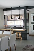 View past dining table into open-plan kitchen with breakfast bar and bar stools