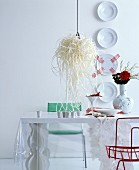 Decorative wall plates and designer lamp in white, futuristic dining room