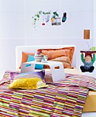 Colourful textiles in bedroom with garden-gnome bedside table
