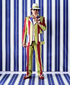 Man wearing brightly striped suit and hat against blue and white striped wall