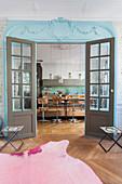 Blick durch farbige Doppeltür mit Sprossenfenstern in die Küche