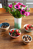 Strauß mit pinken Anemonen und Schalen mit Erdbeeren und Nüssen