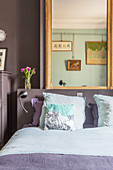 Alte Kommode neben dem Bett im zweifarbigen Schlafzimmer