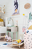 Vintage bedside table, cot and animal motifs in child's attic bedroom