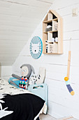 Display case on white-painted wooden wall in child's attic bedroom
