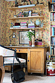 Desk and shelves against wall with floral wallpaper