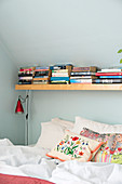 Books on shelf above bed under sloping ceiling