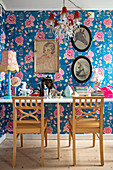 Ornaments on table and two chairs in front of pictures on floral wallpaper
