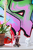 Anatomic model, model skull and guitar in front of graffito on wall