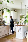 Frau steht in weißer Küche mit vielen Zimmerpflanzen