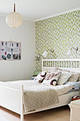 White bed against green-patterned wall in vintage-style bedroom