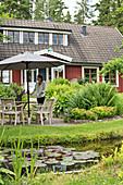 Teich und Terrassenplatz vor Schwedenhaus mit Gaubenfenster