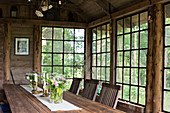 Large wooden table and chairs in rustic orangery with lattice windows