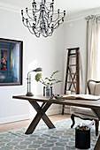 Elegantes Arbeitszimmer mit Holztisch und Kronleuchter