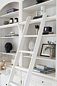 Elegant ornaments on white shelves with library ladder