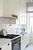 Vintage-style gas cooker in bright country-house kitchen with white cupboards