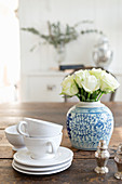 Stack of white teacups and saucers and Oriental vase of white roses on wooden table