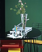 Glass vase and glass pen holders in front of green wall