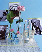 Water bottles used as vases in front of photos on blue wall
