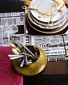 Geschirr und Besteck in Gold auf Zeitungspapier