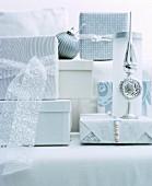 Verpackte Geschenke und Christbaumschmuck in Weiß und Silber