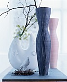 Branches in vases and china bird in nest of twigs