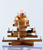 Lit candles and stag figurine on wooden Christmas tree