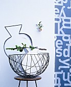 Vase and branch of unripe figs in delicate wire basket
