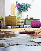 Cowhide rug on floor of colourful living room with staghorn fern hung from ceiling