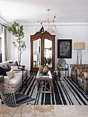 Antique, carved cupboard with mirrored doors and pale couch in comfortable living room