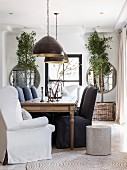 Black and white loose-covered chairs around exotic-wood table in front of windows and round mirrors
